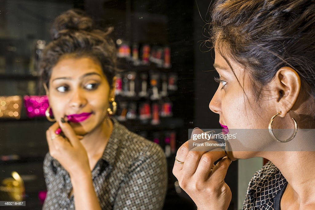 A portrait of a beautiful young Muslim woman putting make-up on her face, working in a make-up shop in one of the new shopping malls.