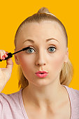 Portrait of a beautiful young woman applying mascara over yellow background