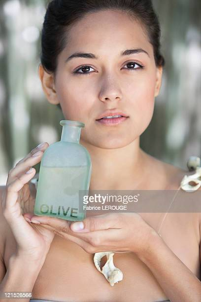 Portrait of a beautiful young woman holding bottle of olive oil