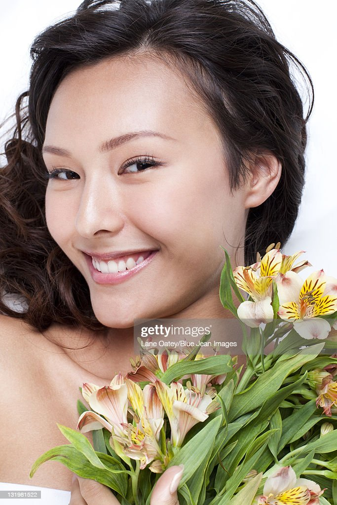 Portrait Of A Beautiful Young Woman Holding Flowers Stock ...