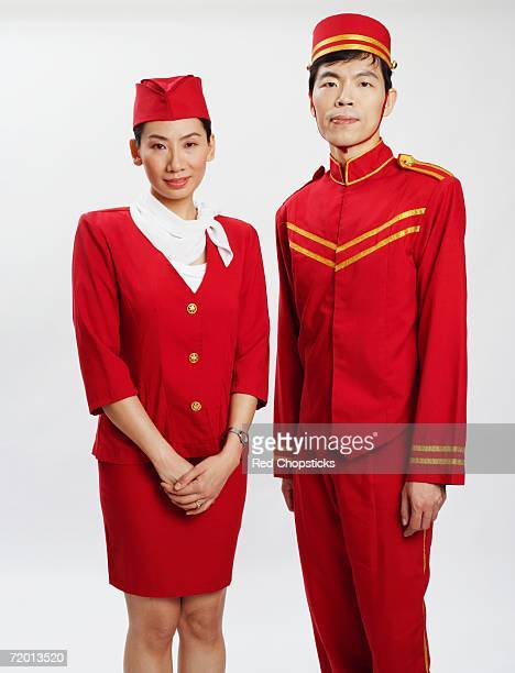 Portrait of a bellhop and an air stewardess standing together and posing