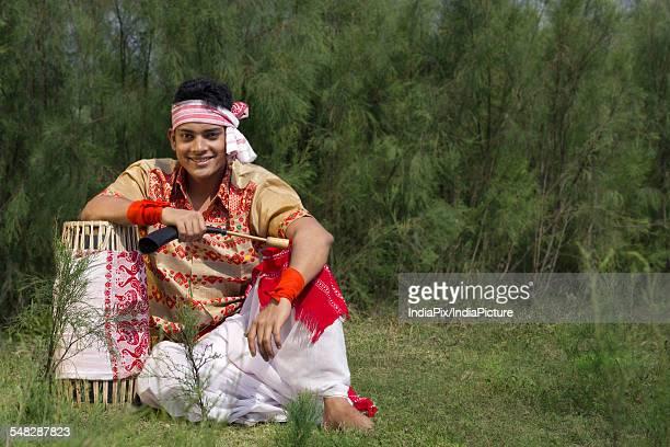 Portrait of a Bihu dancer sitting with a dhol