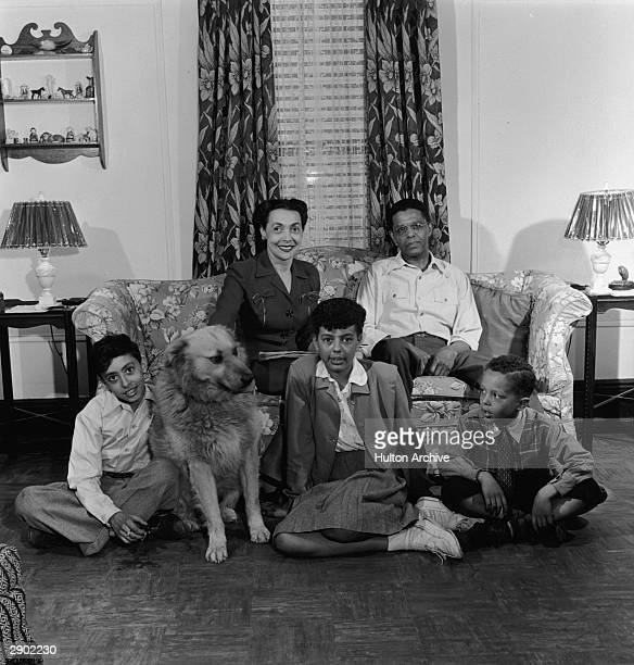 Portrait of a Black family seated in their living room circa 1950 The parents sit on a sofa with their children and dog on the floor