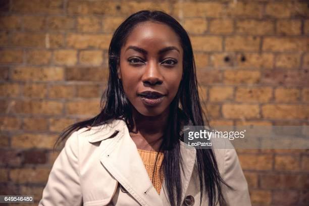 Portrait of a black woman against a brick wall