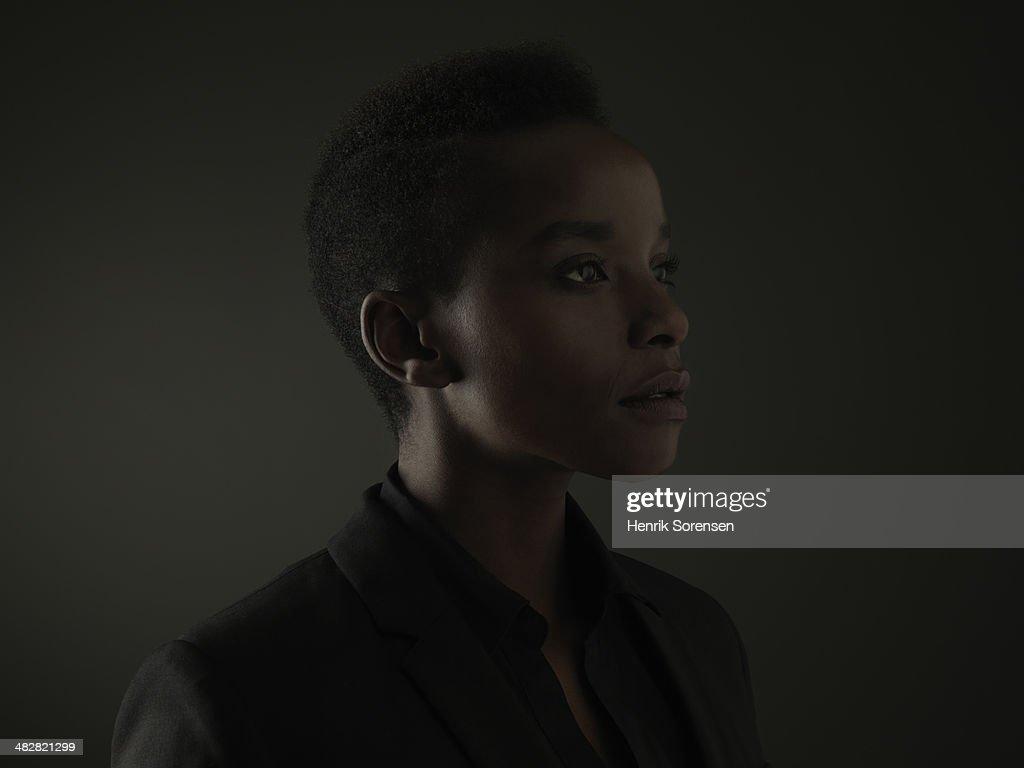 Portrait of a black woman on a dark backdrop : Stock Photo