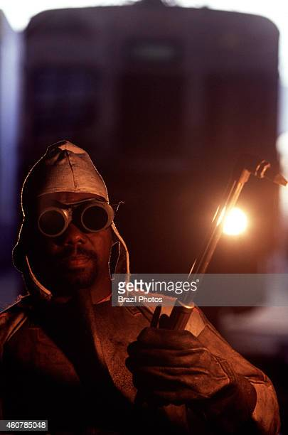 Portrait of a black worker who is a welding employee of the railway using a blowtorch