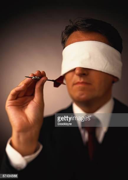 portrait of a blindfolded businessman holding a dart