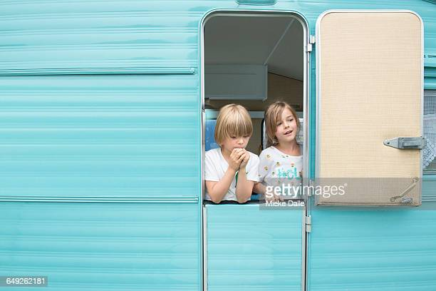 Portrait of a boy and a girl at caravan door