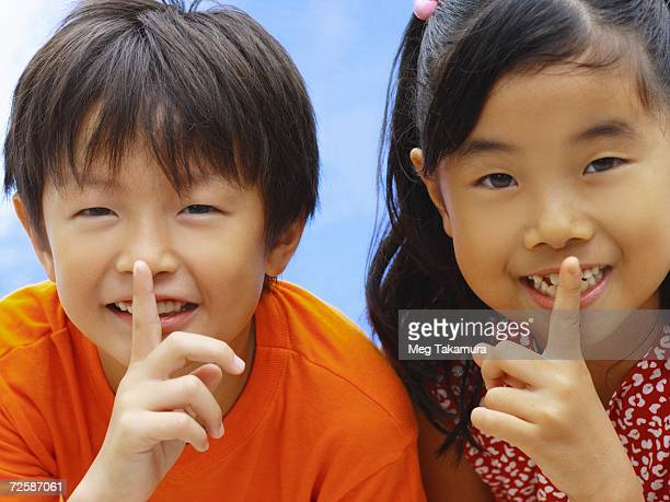 Portrait of a boy and girl with their fingers on their lips