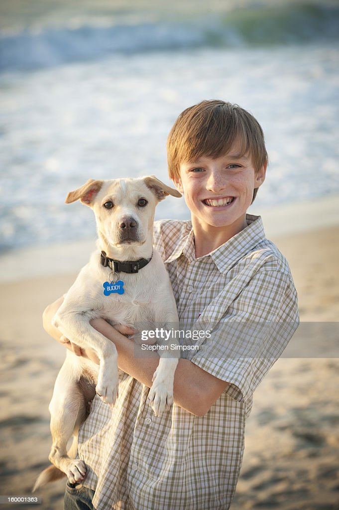 portrait of a boy and his dog at t he beach : Stock Photo