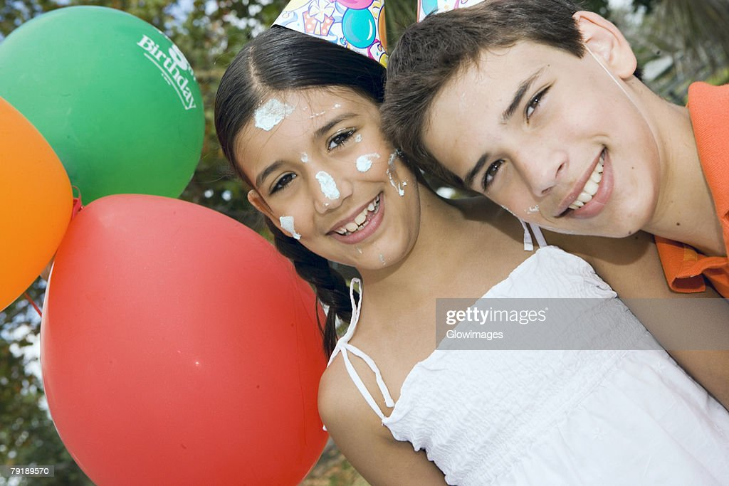 Portrait of a boy and his sister wearing birthday hats and smiling : Foto de stock
