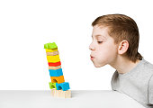 Portrait of a boy blowing on falling house made of wooden blocks