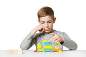 Portrait of a boy building house made of wooden blocks