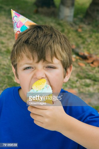 Portrait of a boy eating a cupcake : Stock Photo