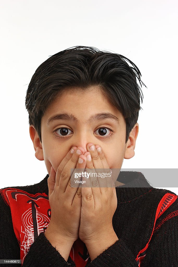 Portrait of a boy, hands on mouth : Stock Photo