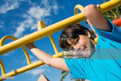 Portrait of a boy hanging on monkey bars and smiling : Foto de stock