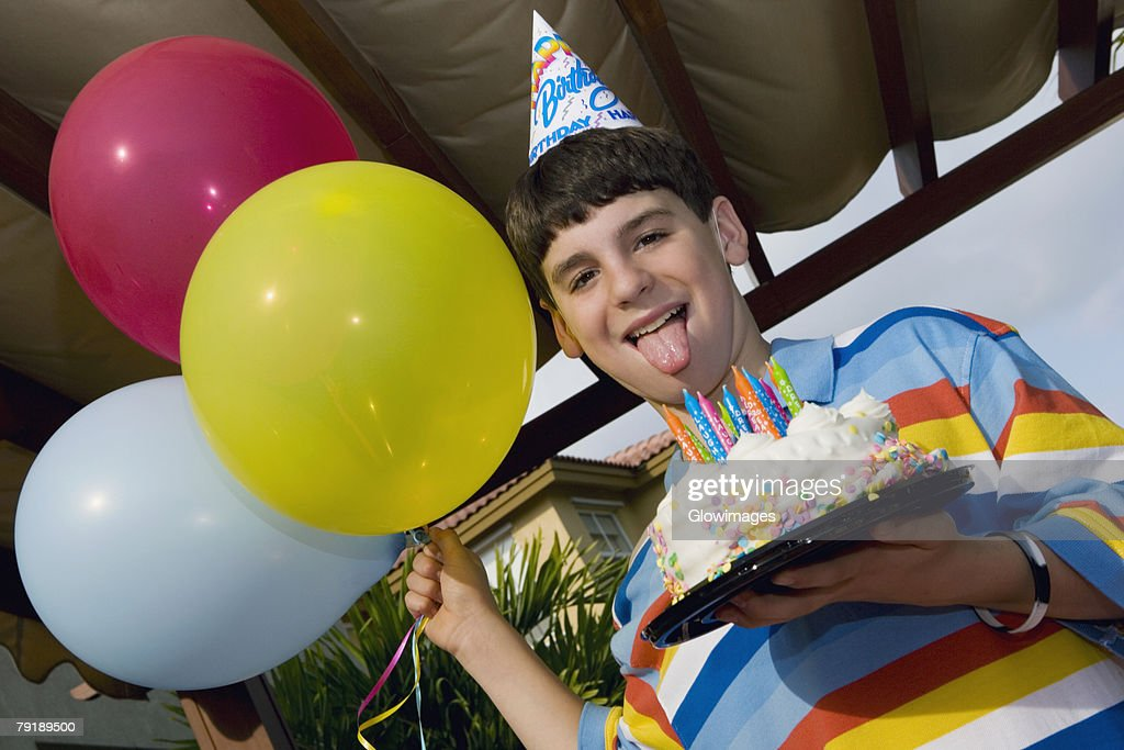 Portrait of a boy holding a birthday cake and balloons : Stock Photo