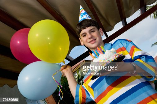 Portrait of a boy holding a birthday cake and balloons : Foto de stock