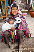 Portrait of a boy holding a lamb and smiling, Pisaq, Urubamba Valley, Peru