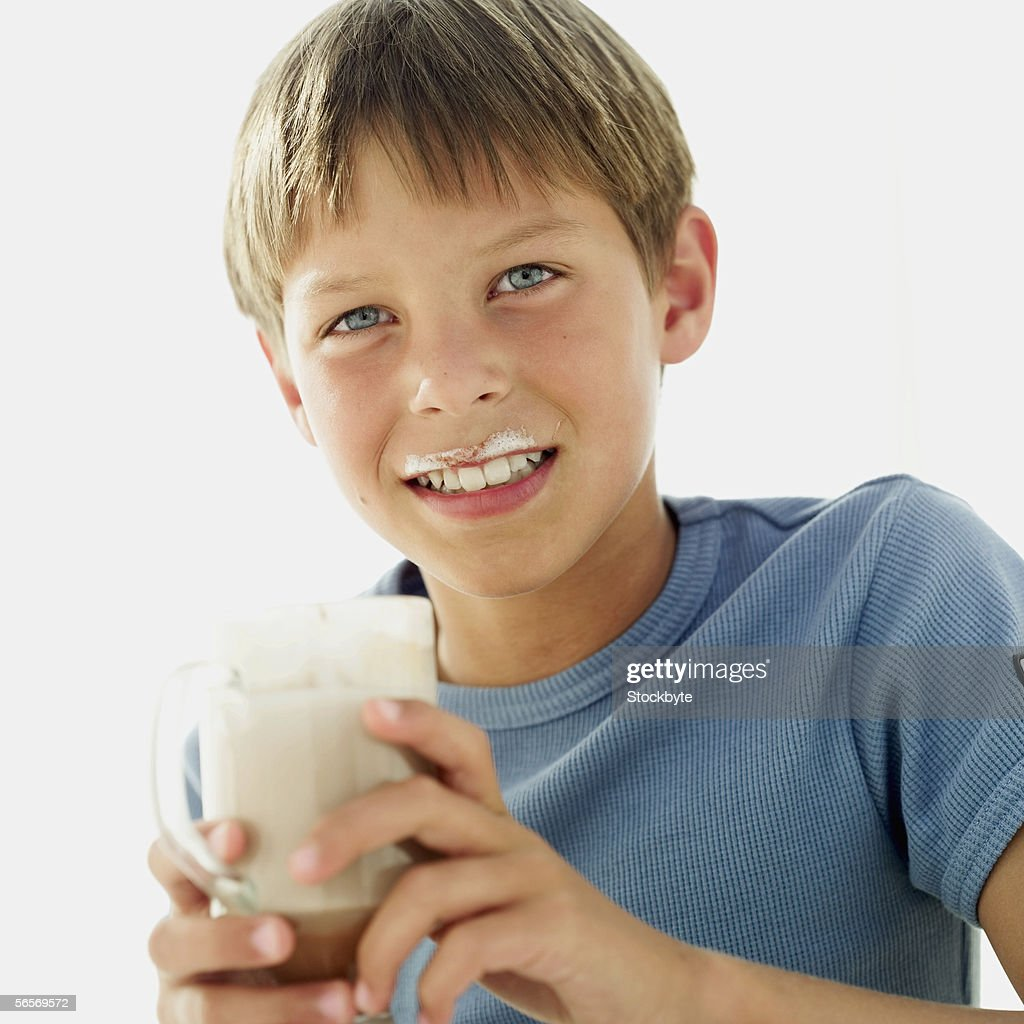 portrait of a boy holding a mug of milk