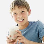 portrait of a boy holding a mug of milk