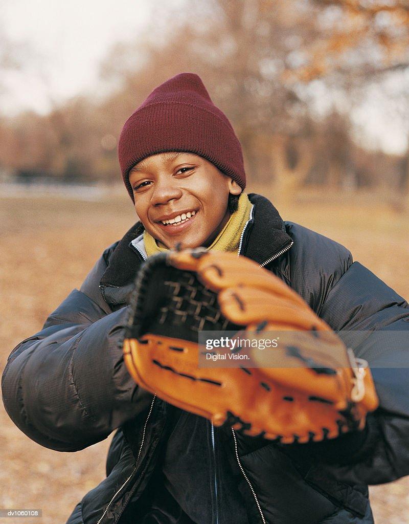 Portrait of a Boy in a Park wearing a Baseball Glove