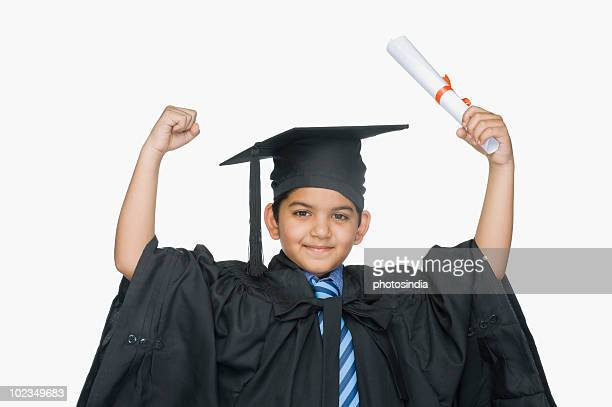Portrait of a boy in graduation gown holding a diploma