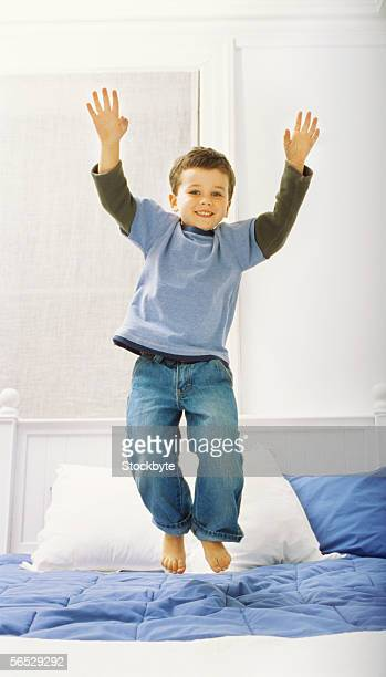 portrait of a boy jumping on a bed