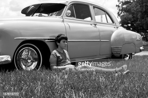 Portrait of a boy laying on the car in black & white picture