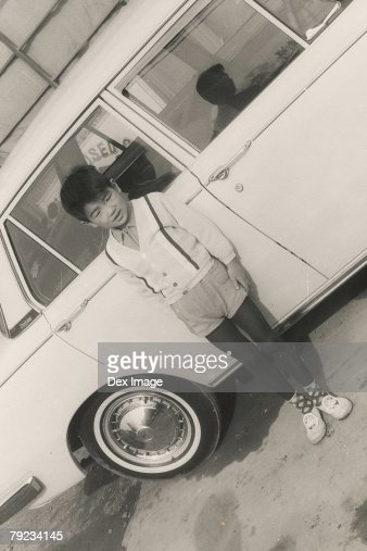 Portrait of a boy leaning against car : Stock Photo