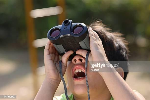 Portrait of a boy looking through binoculars