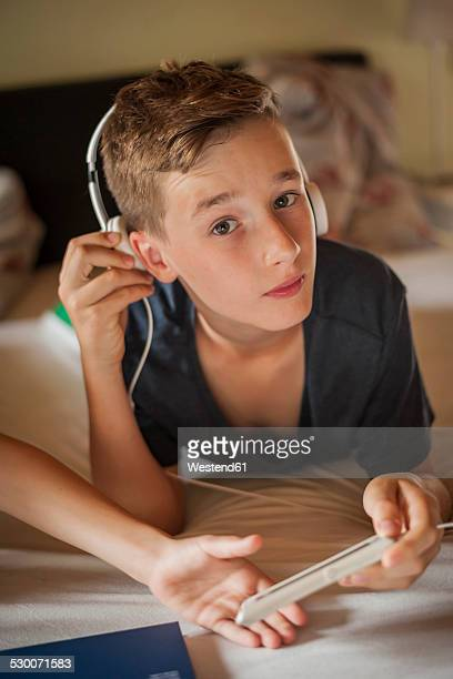Portrait of a boy lying on bed hearing music with head phones