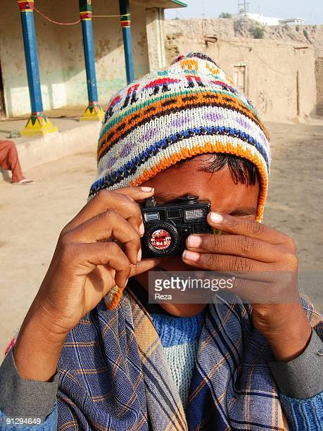 Portrait of a boy posing with a camera for the camera on January 2007 in Sehwan Sharif Pakistan