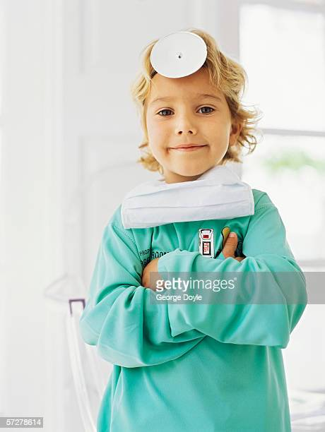 Portrait of a  boy pretending to be a doctor, standing with his arms folded
