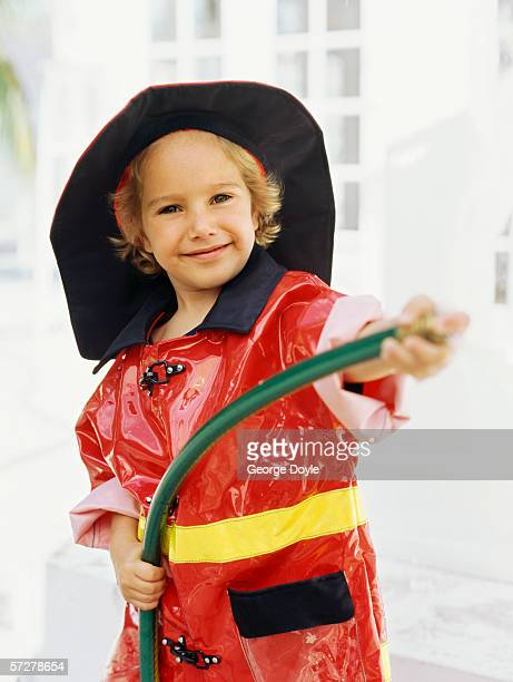 Portrait of a boy pretending to be a fireman, holding a hose