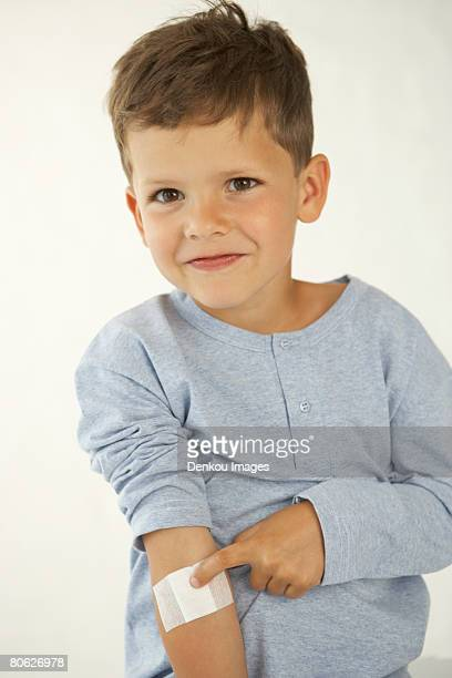 Portrait of a boy showing an adhesive bandage on his hand