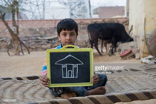 Portrait of a boy showing chalk drawing of house on a slate, Hasanpur, Haryana, India
