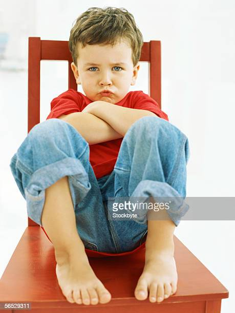 portrait of a boy sitting on a chair, puckering his lips