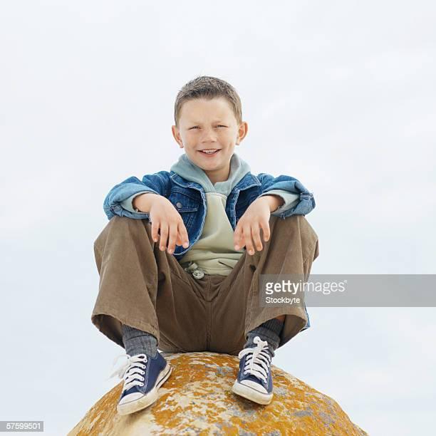 portrait of a boy sitting on a rock