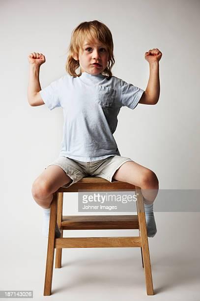 Portrait of a boy sitting on a stool.