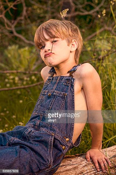 Young boy wearing overalls on fallen tree with grass straw in mouth
