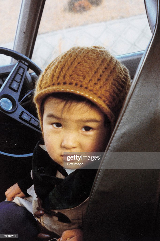 Portrait of a boy sitting on driver's seat : Stock Photo