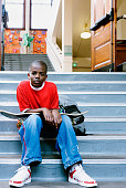 Portrait of a boy sitting on stairs and holding a skateboard