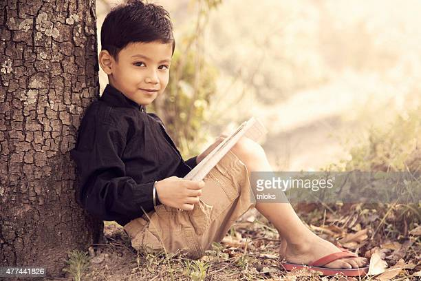 Portrait of a boy sitting under tree and reading book