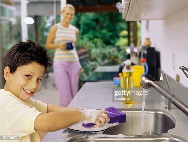 Portrait of a boy washing dishes in the kitchen sink