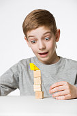 Portrait of a boy watching house made of wooden blocks fall