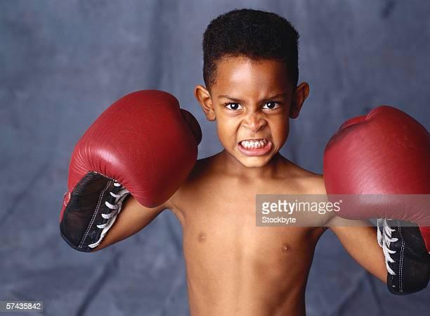 portrait of a boy (6-8) wearing boxing gloves
