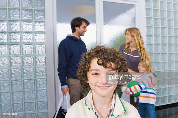 Portrait of a boy with his parents in the background