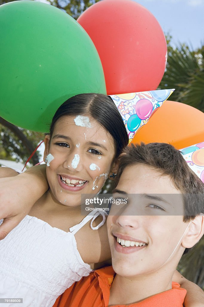 Portrait of a boy with his sister wearing birthday hats and smiling : Foto de stock
