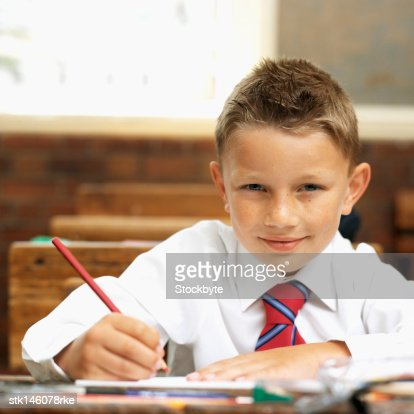 Portrait of a boy (9-11) writing in a classroom